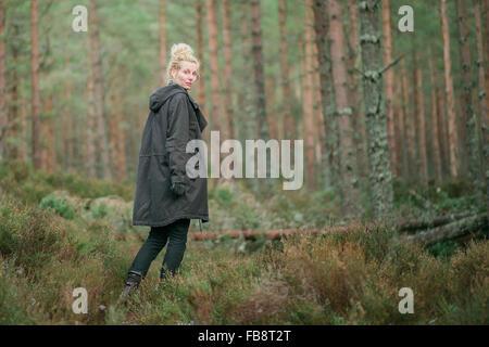 Eine Frau Wanderer zu Fuß durch einen Kiefernwald in Schottland - Stockfoto
