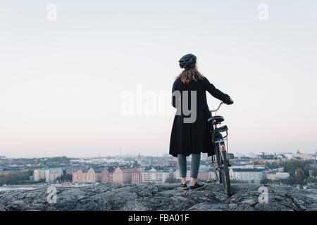 Schweden, Sodermanland, Stockholm, Sodermalm, Skinnarviksberget, hinten anzeigen der jungen Frau, die mit dem Fahrrad - Stockfoto