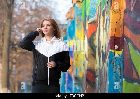 Jogger-Mädchen in Sportbekleidung anziehen Kopfhörer vor morgen joggen Praxis auf der Straße neben hellen Graffitiwand - Stockfoto