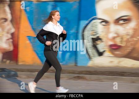 Schöne sportliche Mädchen tragen Läufer Sportbekleidung im Ohrhörer in der Stadt von morgen durch helle Graffitiwand, - Stockfoto