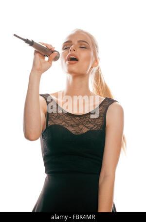 junge hübsche blonde Frau im Mikrofon singen isoliert schließen schwarze Kleid Karaoke Mädchen - Stockfoto