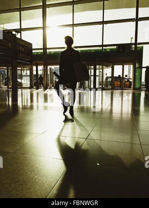 Rückansicht des jungen Frau, die am Flughafen - Stockfoto