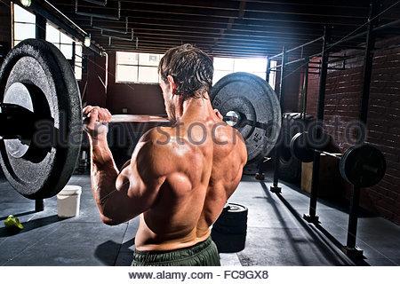 Ein Crossfit Athlet führt Bizeps locken. - Stockfoto