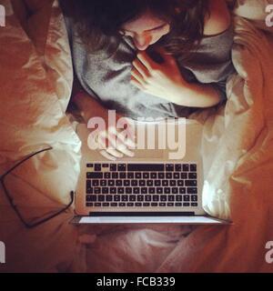 Direkt über die Aufnahme der jungen Frau mit Laptop am Bett - Stockfoto