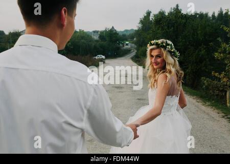 Braut führt Bräutigam, auf der Straße - Stockfoto