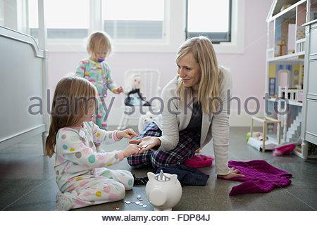 Mutter und Tochter platzieren Münzen im Sparschwein - Stockfoto