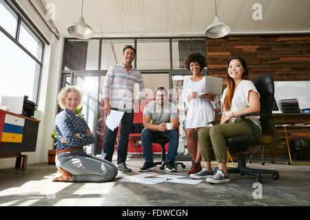 Porträt der glückliche junge Menschen in einer Besprechung Blick in die Kamera und lächelnd. Junge Designer arbeiten - Stockfoto
