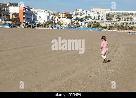 Mädchen spielen auf Strand Carihuela in Winter Saison, Torremolinos, Costa Del Sol, Spanien. - Stockfoto