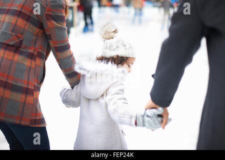 Rückansicht des Mädchen-Eislaufen mit Eltern, Hand in Hand - Stockfoto