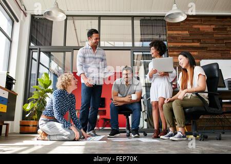Gruppe von kreativen Menschen diskutieren neues Projekt. Frau sitzt mit dokumentiert locker am Boden und während - Stockfoto