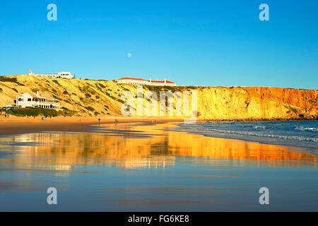 Menschen am Ocean Beach bei Sonnenuntergang. Vollmond am Himmel.  Portugal - Stockfoto