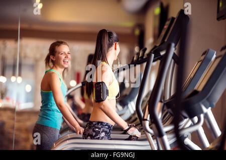 Zwei passen Frauen laufen auf Laufbändern im modernen Fitnessraum - Stockfoto