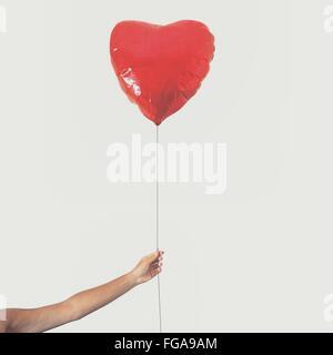 Hand, die roten Herzballon Form gegen klaren Himmel beschnitten - Stockfoto