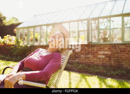Unbeschwerte senior Frau entspannende außerhalb sonnigen Gewächshaus - Stockfoto
