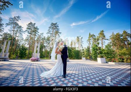 elegante stilvolle Bräutigam mit seiner glücklich wunderschöne Braut Küsse im park - Stockfoto