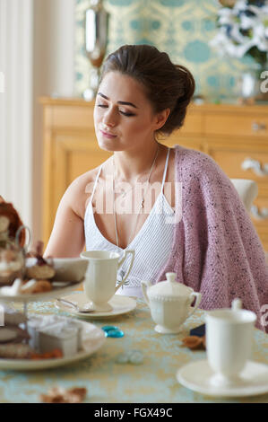 schöne Frau am Morgen in der Küche sitzen und Tee trinken - Stockfoto