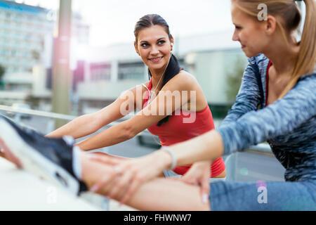 Zwei Frauen Dehnen der Muskeln vor dem Joggen - Stockfoto