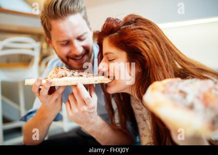 Paar Teilen Pizza und Essen zusammen glücklich - Stockfoto