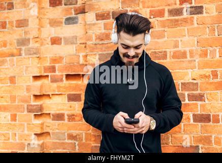 Porträt des jungen Mannes vor Ziegel Wand Musik hören mit Kopfhörern - Stockfoto