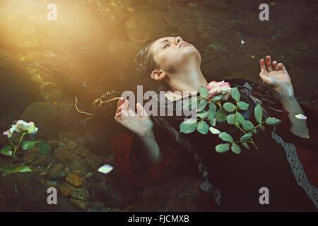 Frau im dunklen Wasser-Strom und weiche Sonnenlicht. Romantik und Tragik - Stockfoto
