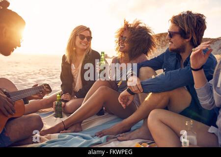 Porträt der Gruppe junger Freunde mit einer Party am Strand abends. Männer und Frauen trinken Bier und Freund anhören - Stockfoto