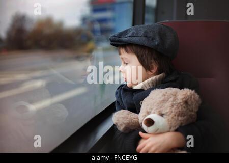 Süßes kleines Kind, Vorschule junge, Reiten in einem Bus, tagsüber, hält Teddybär - Stockfoto