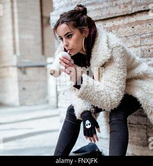 ziemlich stylish Teenagers Mädchen außerhalb auf Stadt Straße fancy Mode gekleidet trinken Milch-shake - Stockfoto