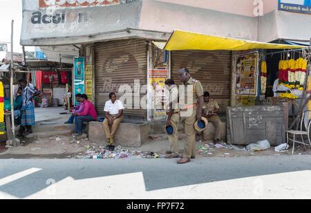 3 Polizisten an einer Straßenecke in Maduranthakam, Kancheepuram Bezirk von Tamil Nadu, mit der lokalen Bevölkerung - Stockfoto