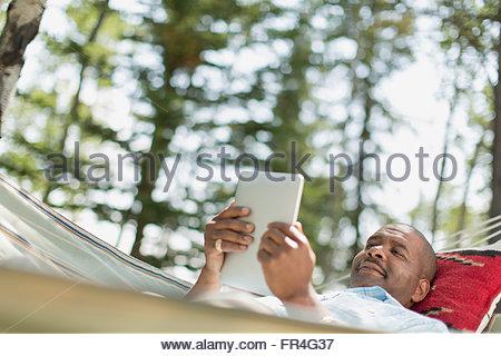 Afrikanische amerikanische Mann mit pc Tablette in der Hängematte. - Stockfoto