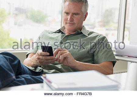 Entspannte Geschäftsmann SMS auf Handy im Büro. - Stockfoto