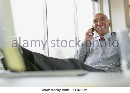 Reife asiatische Geschäftsmann mit Füße hoch auf Schreibtisch. - Stockfoto