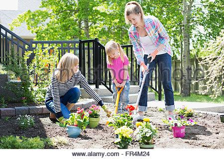 drei Generationen von Frauen, die Arbeiten am Blumengarten - Stockfoto