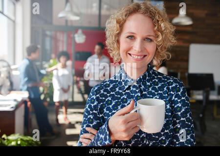Porträt der glückliche junge Geschäftsfrau hält eine Tasse Kaffee, Blick in die Kamera und lächelnd. Sie steht in - Stockfoto