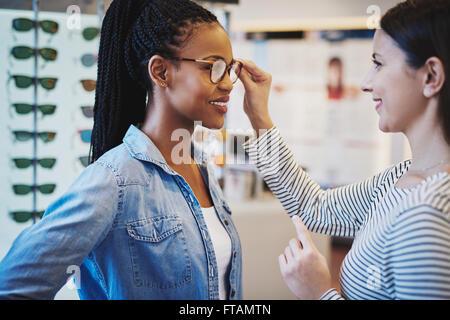 Augenarzt helfen einen ziemlich afrikanischen Client anprobieren und Rahmen für eine Brille zu kaufen - Stockfoto