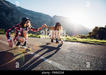 Glückliche junge Paare, die Spaß mit Skateboard auf der Straße. Junger Mann und Frau zusammen an einem sonnigen - Stockfoto