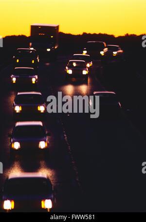 Scheinwerfer des entgegenkommenden Autobahnverkehr gegen Sonnenuntergang - Stockfoto