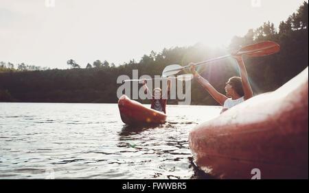 Glückliches junges Paar genießen Kanufahren auf Sommertag. Junger Mann und Frau, die Spaß beim Kajakfahren. - Stockfoto