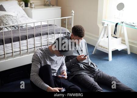 Zwei männliche Studenten im Schlafzimmer überprüfen Sie Nachrichten auf dem Handy - Stockfoto