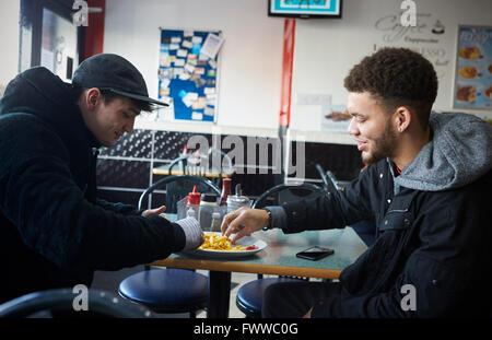 Zwei männliche Studenten Essen im Café - Stockfoto