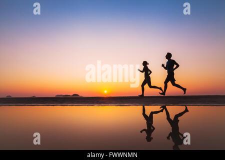 Training, Silhouetten von zwei Läufern am Strand bei Sonnenuntergang, Sport und gesunde Lebensweise Hintergrund - Stockfoto