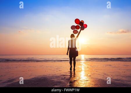 Motivation oder Hoffnung Konzept, folgen Sie Ihrem Traum und Inspiration, Mädchen mit Luftballons bei Sonnenuntergang - Stockfoto