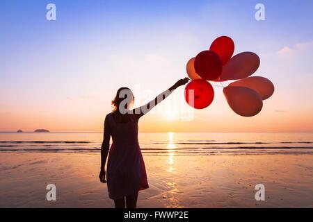 Phantasie und Kreativität, Mädchen mit bunten Ballons bei Sonnenuntergang mit Exemplar, Inspiration Konzept - Stockfoto