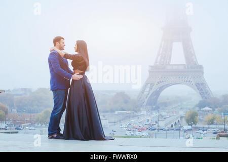 glückliches Paar in Paris zu reisen, Lust auf lächelnder Mann und Frau posiert in modischer Kleidung auf Eiffelturm - Stockfoto