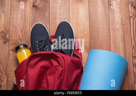 Sporttasche mit Sportgeräten: Schuhe, Flasche, Fitness-Matte auf Holzboden - Stockfoto