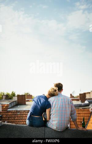 Deutschland, Berlin, junges Paar sitzt auf Dachterrasse mit Bier - Stockfoto