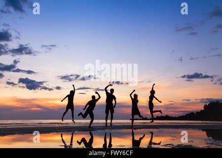 Gruppe von Menschen springen am Strand bei Sonnenuntergang, Silhouette von Freunden gemeinsam Spaß haben - Stockfoto