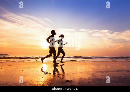 Sport und gesunde Lebensweise, zwei Menschen, Joggen am Strand bei Sonnenuntergang - Stockfoto