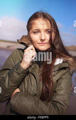 Schöne junge Frau kauern in ihren Mantel an einem windigen Tag am Strand - Stockfoto