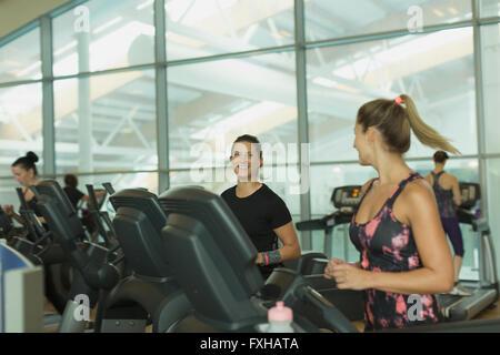 Lächelnde Frauen reden und Joggen auf dem Laufband im Fitnessstudio - Stockfoto