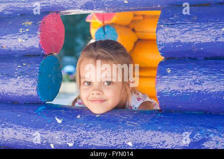 Fünfjähriges Mädchen schaut aus einem Holz-Fenster - Stockfoto